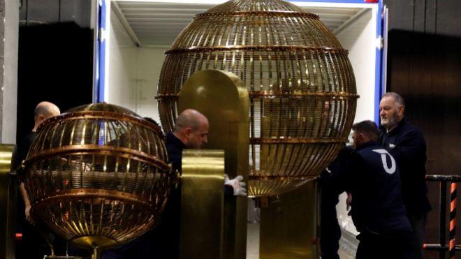 Varios operarios mueven los bombos de la Lotería de Navidad que llegaron ayer al Teatro Real (Madrid).