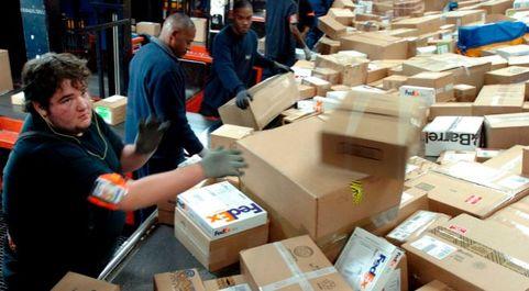 Empleados de FedEx clasificando paquetes en la sede de Memphis,...