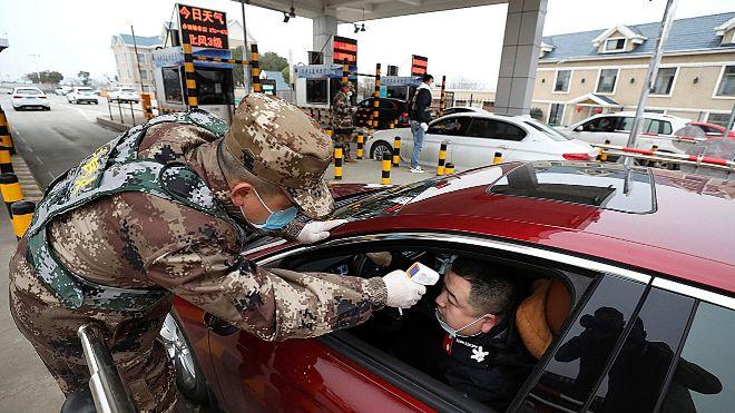 Un militar del régimen chino toma la temperatura de un conductor en...