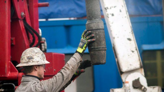 Foto de archivo de un trabajador colocando una tubería en una planta...