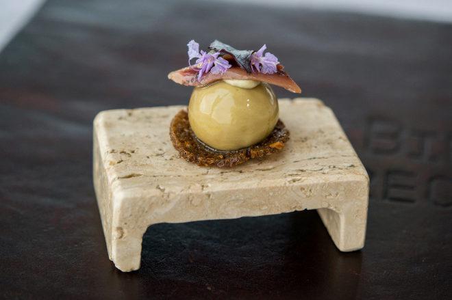 Bombón de alcachofa y oloroso con perejil y pipas de girasol.