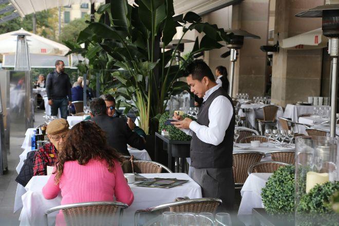 Un camarero atiende a unos clientes en una terraza en la zona de Port...