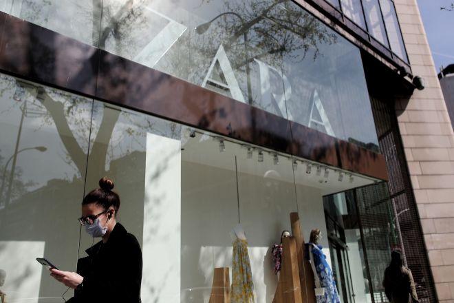 Una mujer con mascarilla pasa junto al escaparate de la tienda de la...