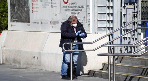 Un hombre protegido con una mascarilla y guantes consulta su móvil.