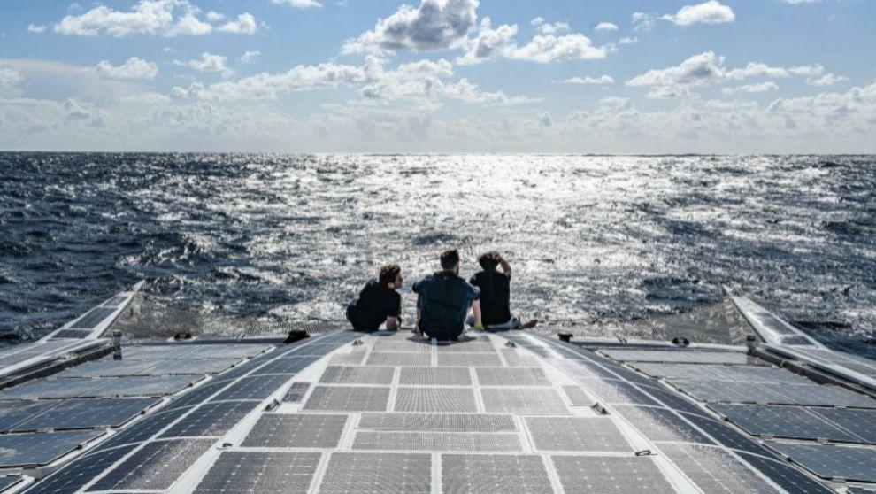 Tres tripulantes del Energy Observer sentandos en la proa de la...