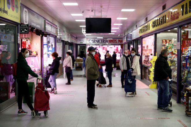 Varias personas protegidas con mascarillas hacen su compra en el...