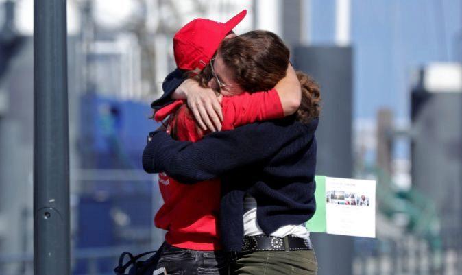 Una estudiante se abraza a un familiar nada más desembarcar del Wylde Swan. | EVA PLEVIER | REUTERS