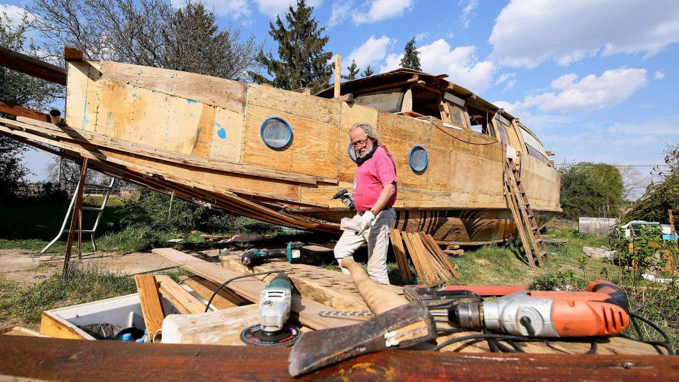 Andrzej Jungst, junto al barco que está construyendo con la madera de...