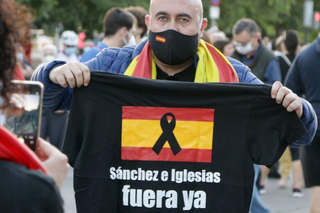 Un hombre muestra una camiseta durante una concentración contra la gestión de Pedro Sánchez y lt;HIT gt;Pablo lt;/HIT gt; lt;HIT gt;Iglesias lt;/HIT gt; en la pandemia en el Paseo de la Alameda de Valencia (España) el 18 de mayo de 2020.