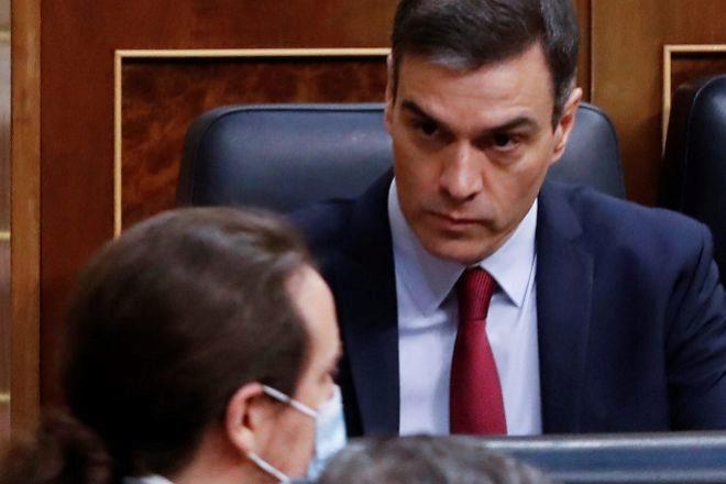 El presidente del Gobierno, Pedro Sánchez, observa pasar al vicepresidente Pablo Iglesias durante la última sesión de control en el Congreso de los Diputados.