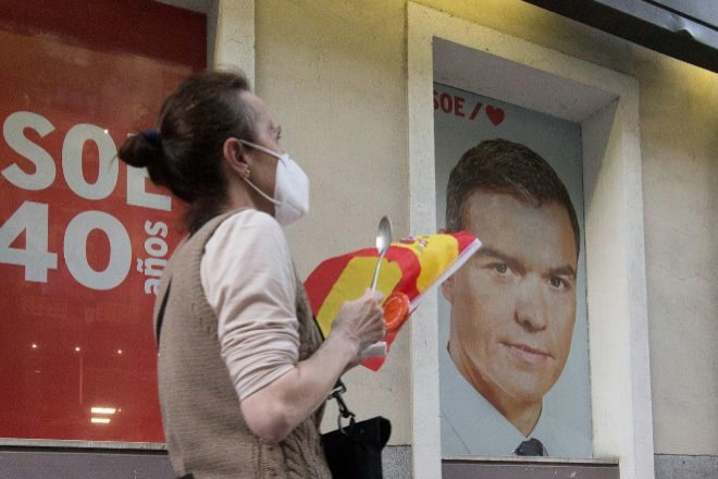 Una mujer protesta delante de un cartel electoral de Pedro Sánchez, en la sede madrileña del PSOE en la calle Ferraz, durante una manifestación en contra de la gestión del Gobierno de la pandemia del coronavirus.