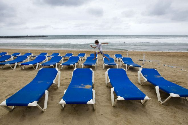 Un niño salta sobre las hamacas vacías en la playa de la Zurriola de San Sebastián.