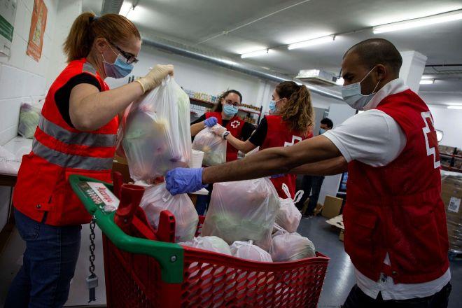 Varios voluntarios preparan lotes de comida en el almacén de la Cruz Roja en Mataró (Barcelona).