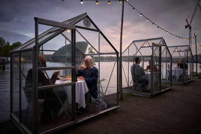 Mesas en casetas de cristal de Mediamatic, restaurante-invernadero en Ámsterdam.