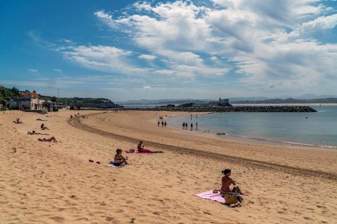 Varias personas en una  lt;HIT gt;playa lt;/HIT gt; manteniendo la distancia social.