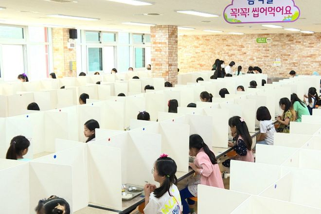Estudiantes comen separados por mamparas en un colegio de Corea del Sur.