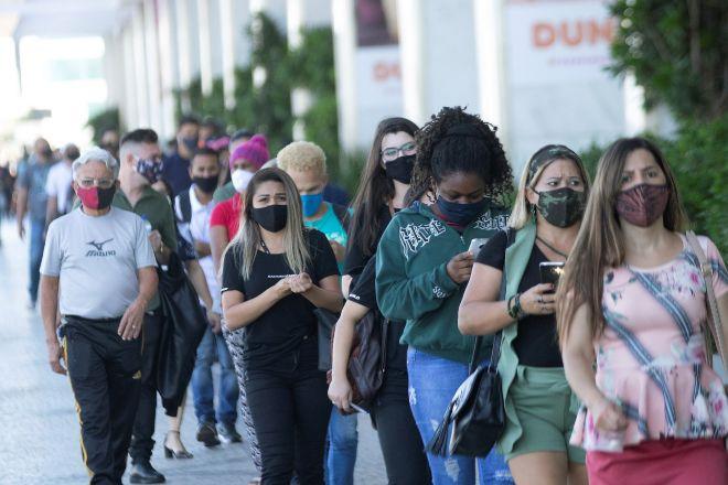 Cientos de personas con mascarillas hacen fila este miércoles en un centro comercial de Brasilia (Brasil).