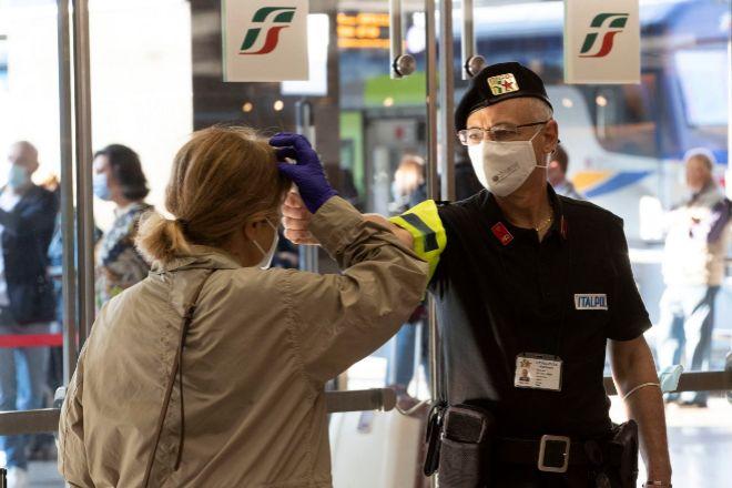 Un policía toma la temperatura a una pasajera en la estación de Termini en Roma.