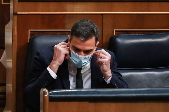El presidente del Gobierno, Pedro Sánchez, se coloca su mascarilla durante la sesión en la que se ejerce el control al Gobierno y se trata la sexta prórroga del estado de alarma por la crisis del Covid-19.