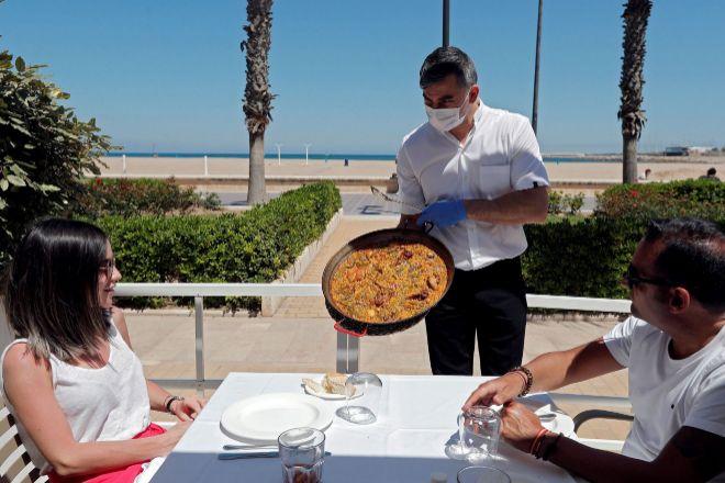 Un camarero sirve una paella en una terraza de un restaurante  de Valencia.