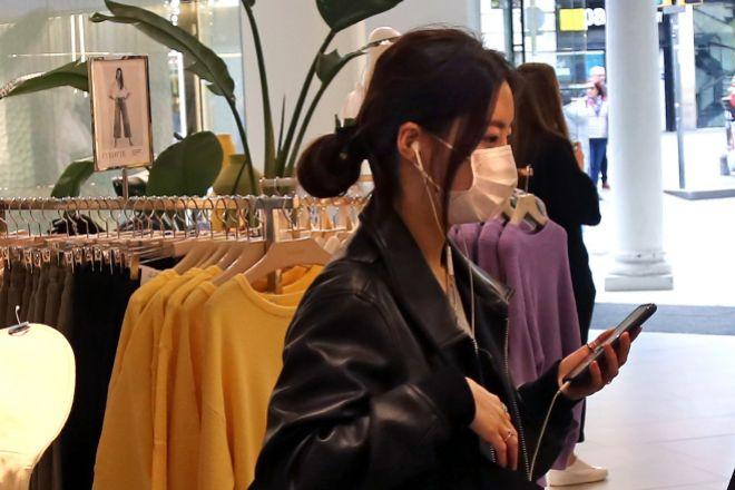 Turista comprando en Barcelona con una mascarilla a mediados de marzo.