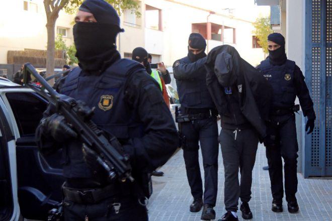 Los Mossos d'Esquadra escoltan a un detenido durante una operación...