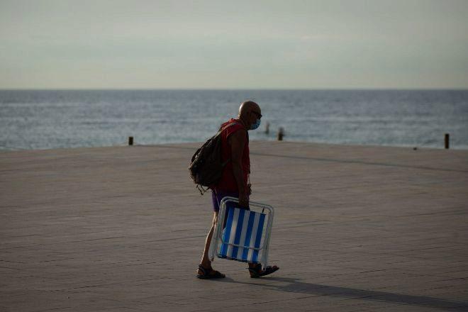 Un ciudadano se dirige hacia la playa de la Barceloneta en Barcelona, inusualmente vacía de turistas