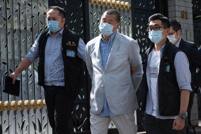El magnate de los medios Jimmy Lai, fundador de Apple Daily, escoltado hoy por agentes de la policía tras su detención hoy en Hong Kong mientras estaba en arresto domiciliario.
