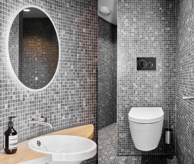 Dos vistas del baño con paredes de mosaico cerámico.