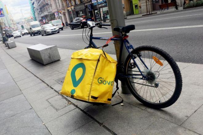 Bicicleta de reparto de Glovo parcada en la calle.