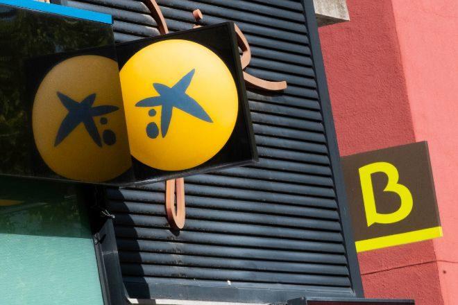 Logos en sucursales de CaixaBank y Bankia