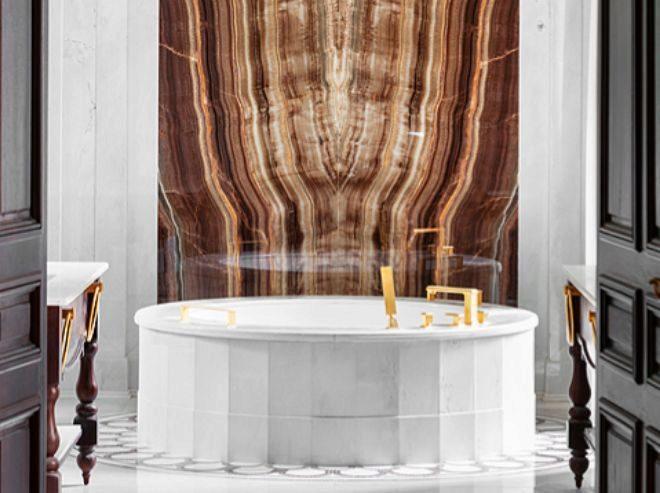 Baño de la Royal Suite, con bañera redonda de mármol y una pared revestida con piedra de ónix Viola.