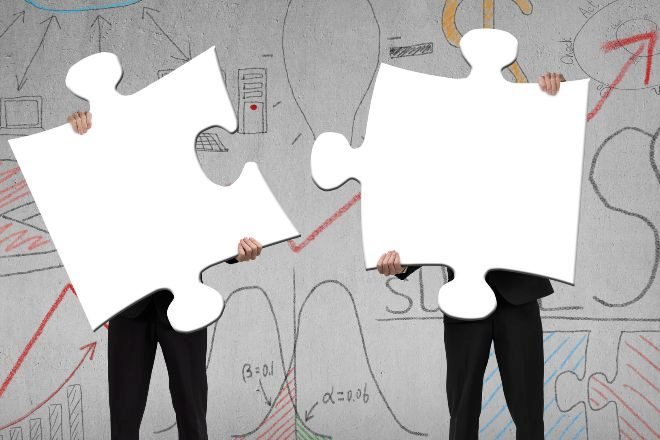 Dos directivos intentan encajar piezas de puzzle