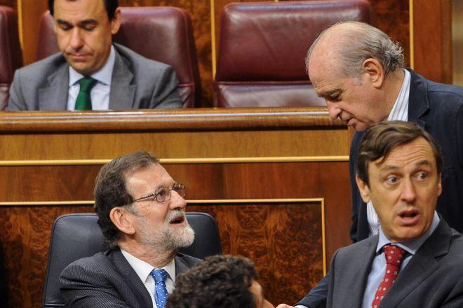 Imagen de archivo del expresidente del Gobierno, Mariano Rajoy (izda.), charlando con el  exministro del Interior, Jorge Fernández Díaz.