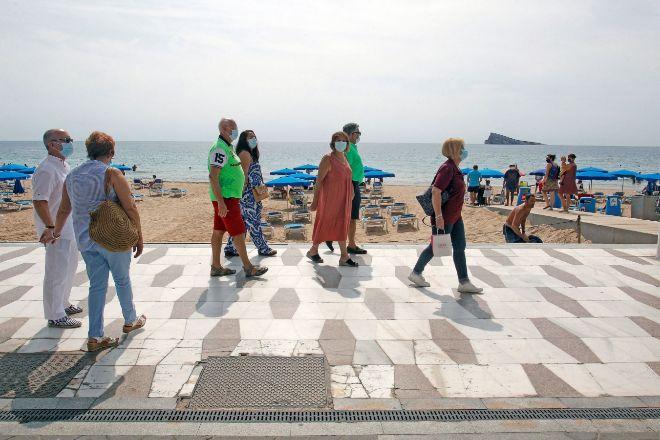 Miembros de  la Asociación Cultural de Mayores de Fuenlabrada) que han organizado su viaje a Benidorm tras la suspensión del programa de viajes del Imserso, ayer paseando por la playa de Levante.