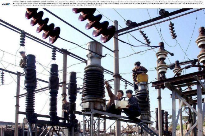 Empleados trabajan en la comprobación y reparación de transformadores eléctricos.