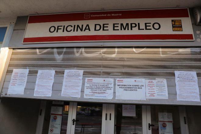 Carteles con diversos avisos en la persiana de cierre de una oficina de empleo en Madrid.