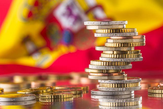 Billetes y monedas delante de una bandera de España.
