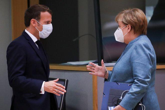 Emmanuel Macron y Angela Merkel se saludan durante la sesión del Consejo Europeo celebrada este jueves en Bruselas.