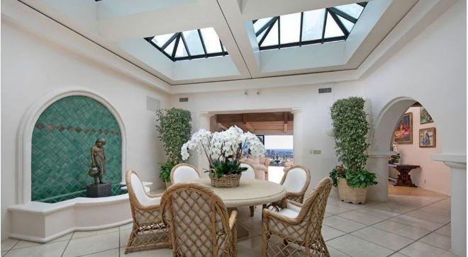 Comedor con una fuente y tragaluces inmensos que iluminan la estancia con luz natural.