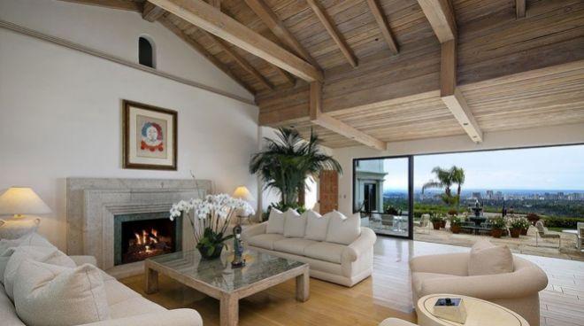 Salón con chimenea y  vigas en el techo que da al patio exterior.