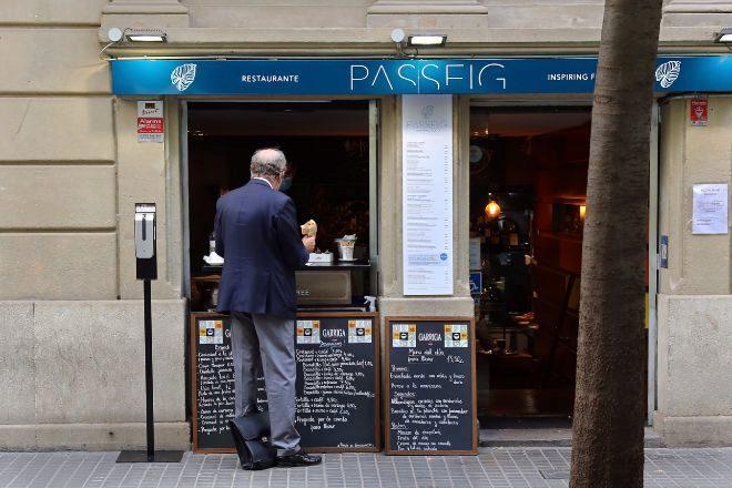 Bar en el centro de Barcelona este lunes, cerrado al público pero que sirve comidas y bebidas para llevar a través de la ventana.