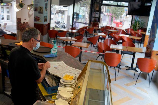 Un camarero lee un periódico en el interior de su bar vacío en Santiago de Compostela (Galicia).
