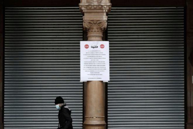 Una persona camina por los porches de la Plaza del Castillo de Pamplona, en la que se observa un cartel avisando del cierre total de la hostelería y la restauración.