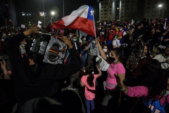 Decenas de personas celebran los resultados del plebiscito constitucional, en el que triunfó una nueva Carta Magna ayer, en Santiago de Chile.