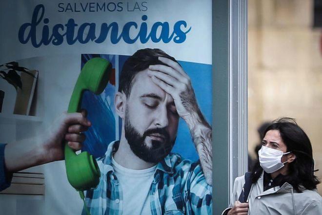 Una mujer pasa junto a un panel publicitario, este lunes en San Sebastiá, ciudad que ha entrado también en zona roja.