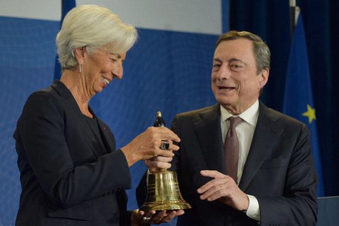 Christine Lagarde, presidenta del BCE, recibiendo hace un año la campana del BCE de manos de Mario Draghi, su predecesor.