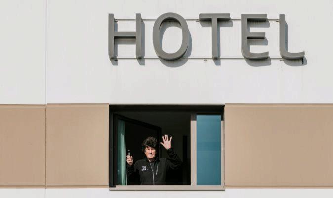 El patrón Jean Le Cam, saludando desde su habitación del hotel donde cumple el confinamiento impuesto por la organización de la regata. | JEAN-LOUIS CARLI / ALEA