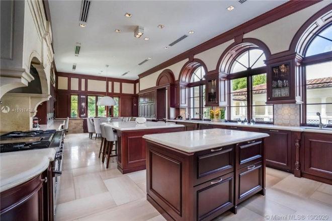 Cocina de estilo italiano y madera noble, con islas dobles y comedor de bancos corridos integrado.