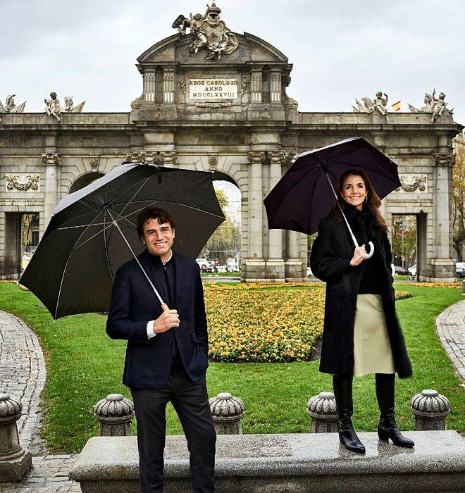 Sandro Silva y Marta Seco, con sendos paraguas, ante la Puerta de Alcalá.